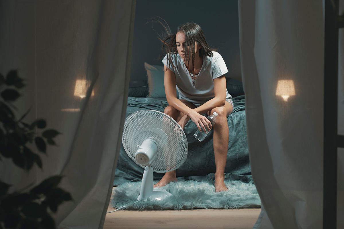 寝室で暑さにやられている女性
