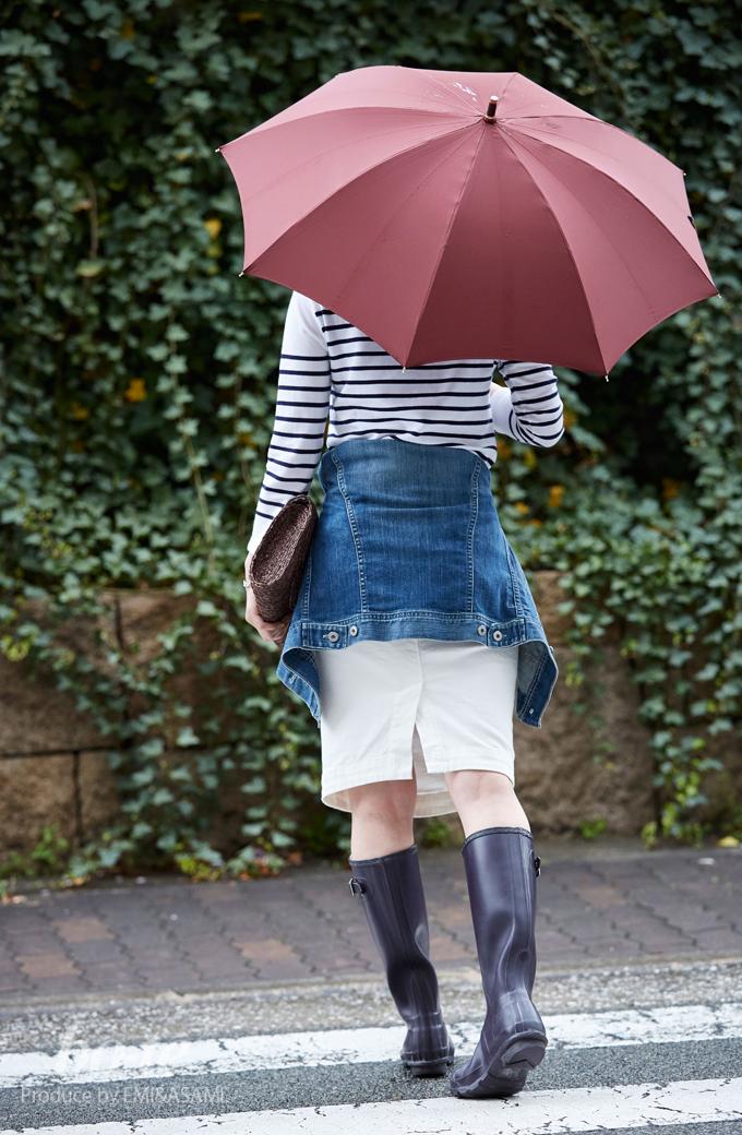 ハンターのブーツを履き傘をさす女性