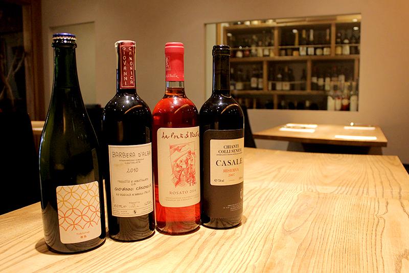 「ワイン棚のスペースが広いので、ついつい気になったワインを買ってしまうんですよ(笑)」と話す星山シェフ。 奥のワイン棚にもギッシリ!