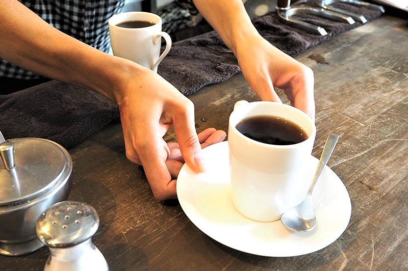 コーヒーを手渡してくれるオーナー