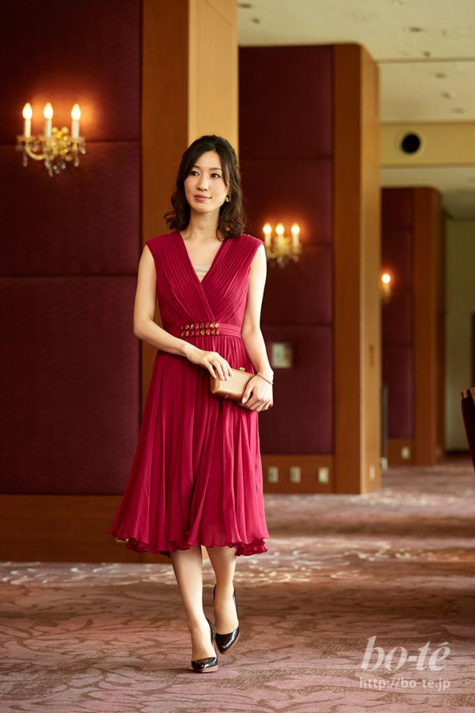 プリーツが上品なワインレッドのドレススタイル