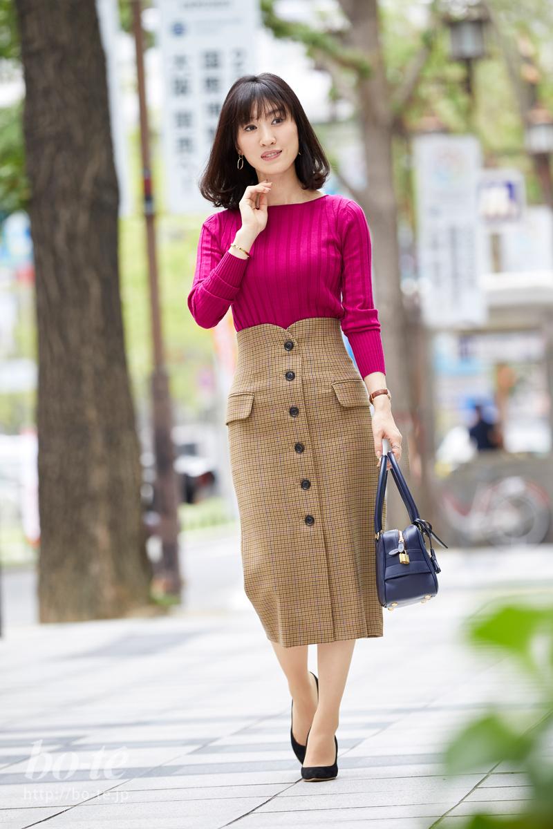 チェック柄のミモレ丈タイトスカートに、パッと艶やかなピンクのトップスをコーデ
