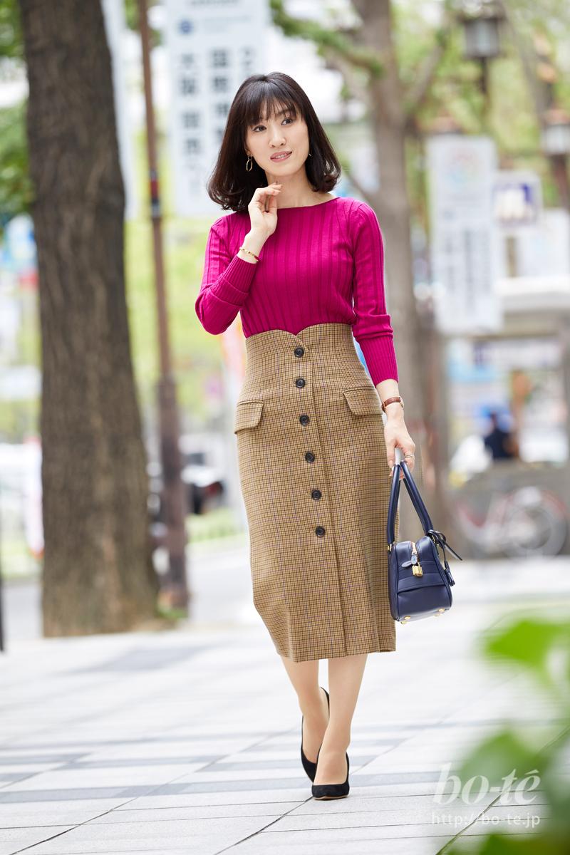 ピンクカラーのニットにチェック柄のスカートを合わせた着こなし