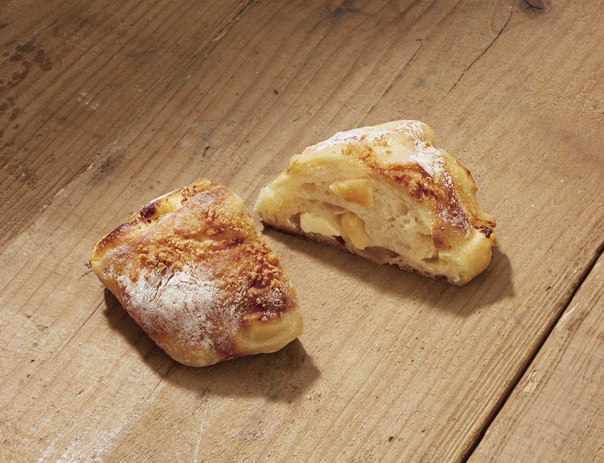10月の新商品「十勝プレミアムシリーズ ポムフロマージュ」(240円)は、北海道・十勝小麦を使用した高加水生地(通常の生地よりも水分量の比率を多くした生地)に青森県産りんごとクリームチーズがイン!