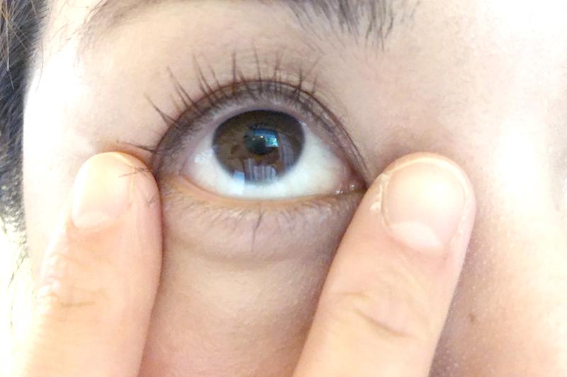 目尻と目頭を指先で押さえる