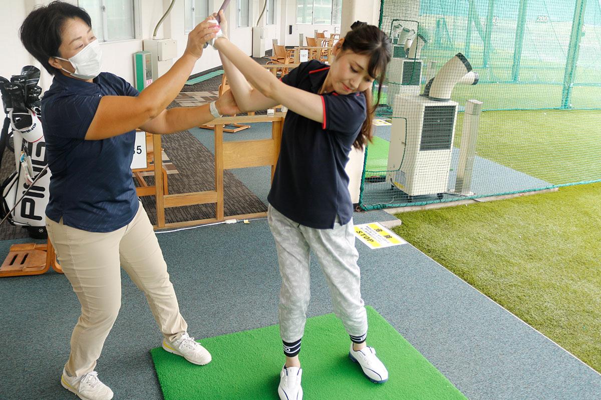 ゴルフレッスンを受けている女性