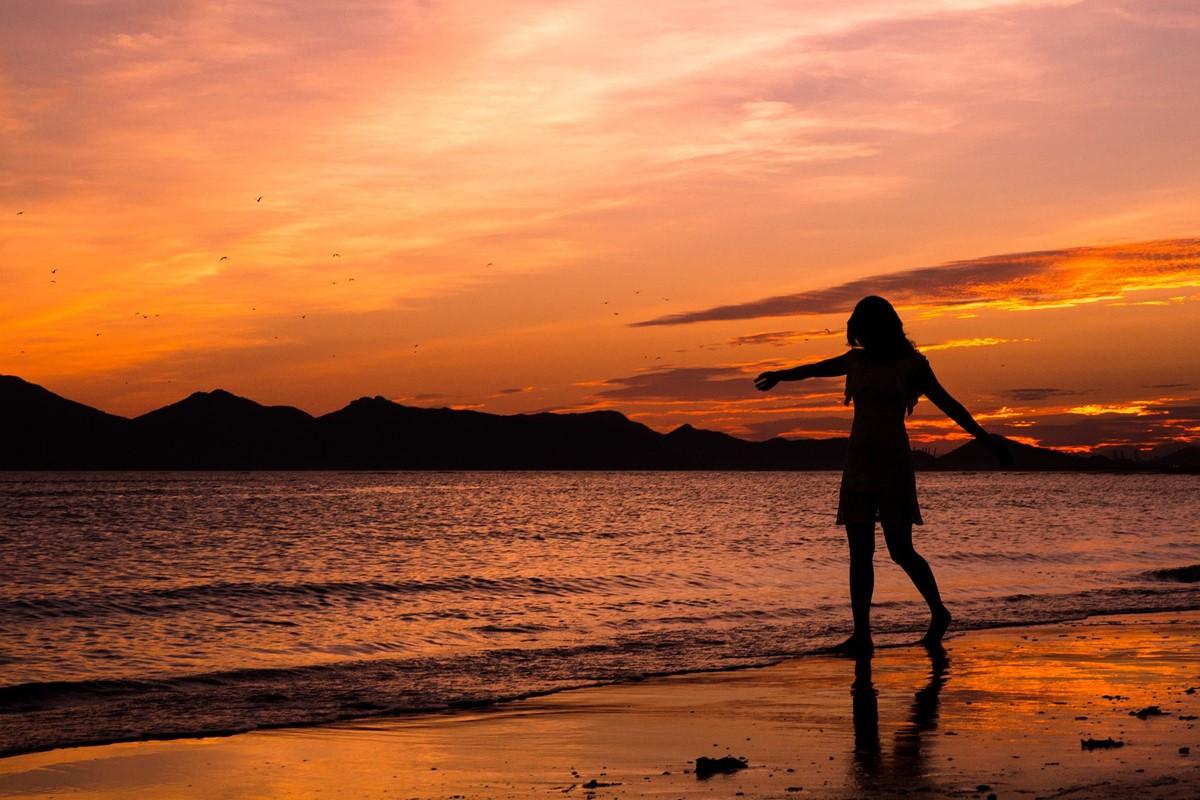 夕焼けの海と女性