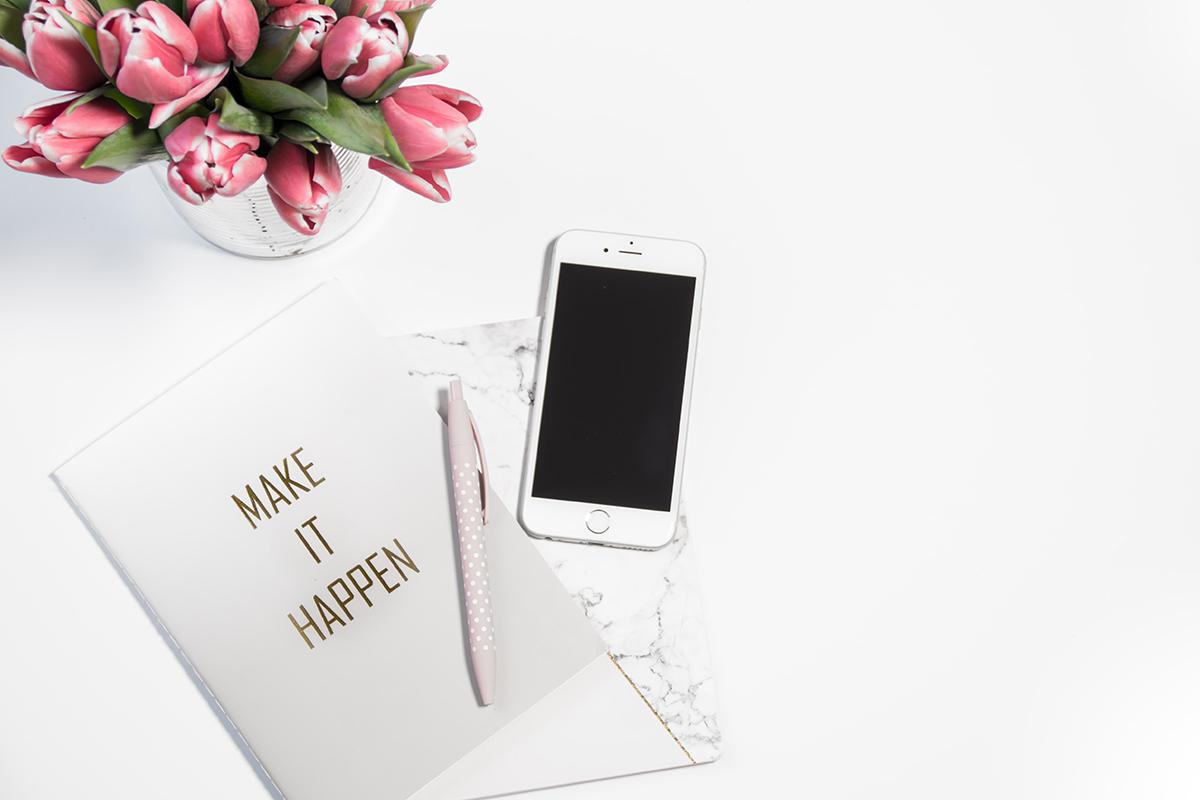 スマートフォンとノートと花瓶が置かれたデスク