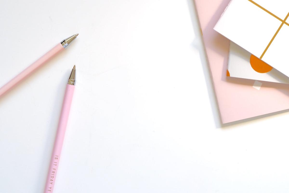 ペンとノートが置かれたデスク