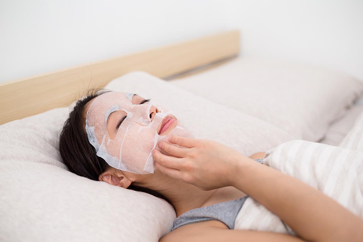 シートマスクをつけて寝る女性