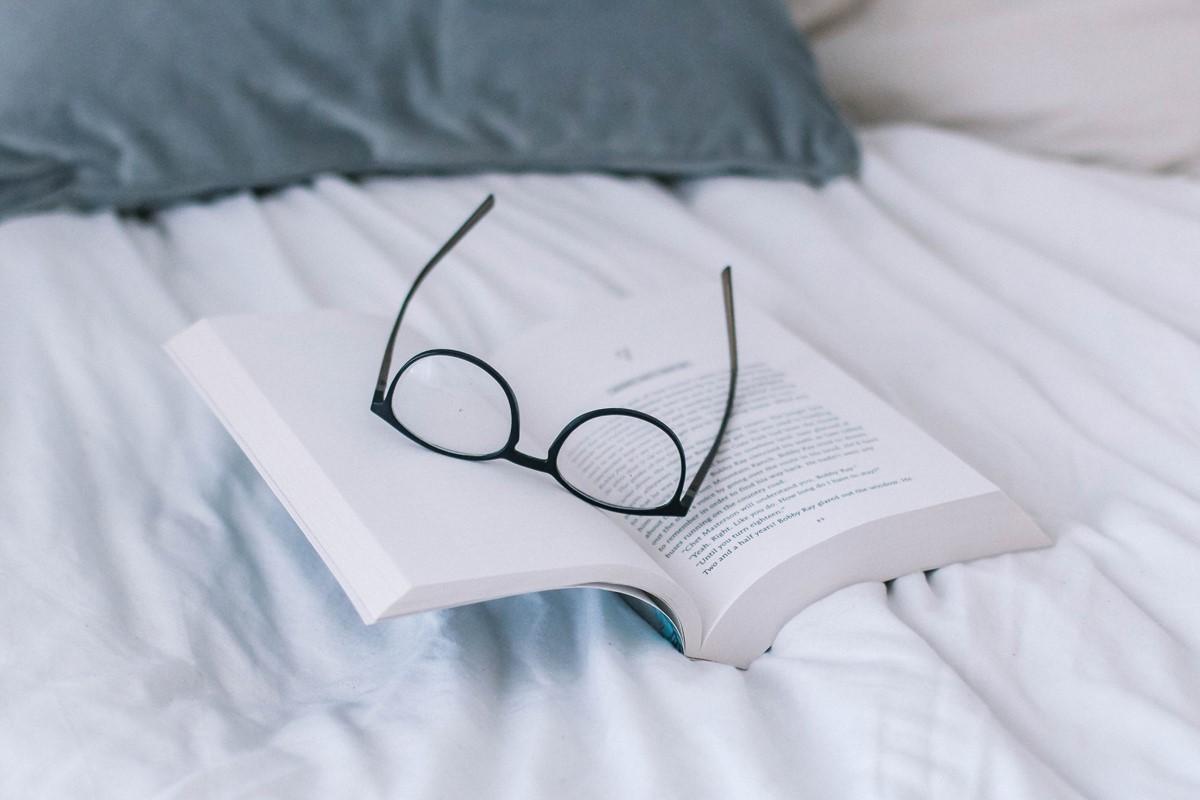 ベッドに置かれた本とメガネ