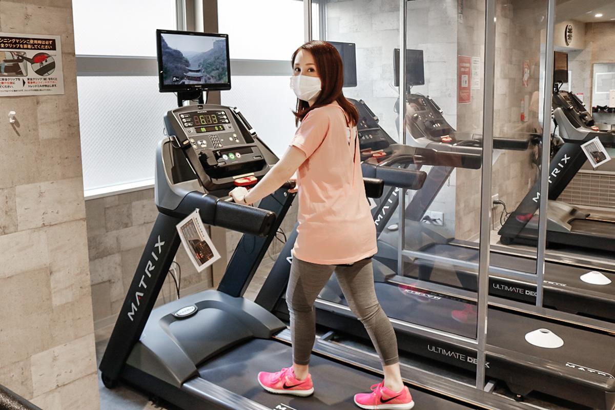 ランニングマシンで歩く女性