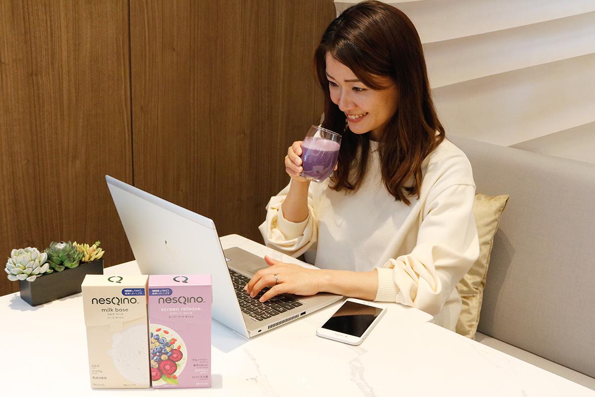 パソコンで仕事をしながらスムージーを飲む女性