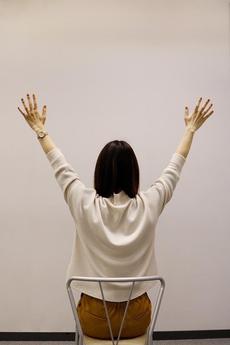 腕を上げてストレッチしている女性