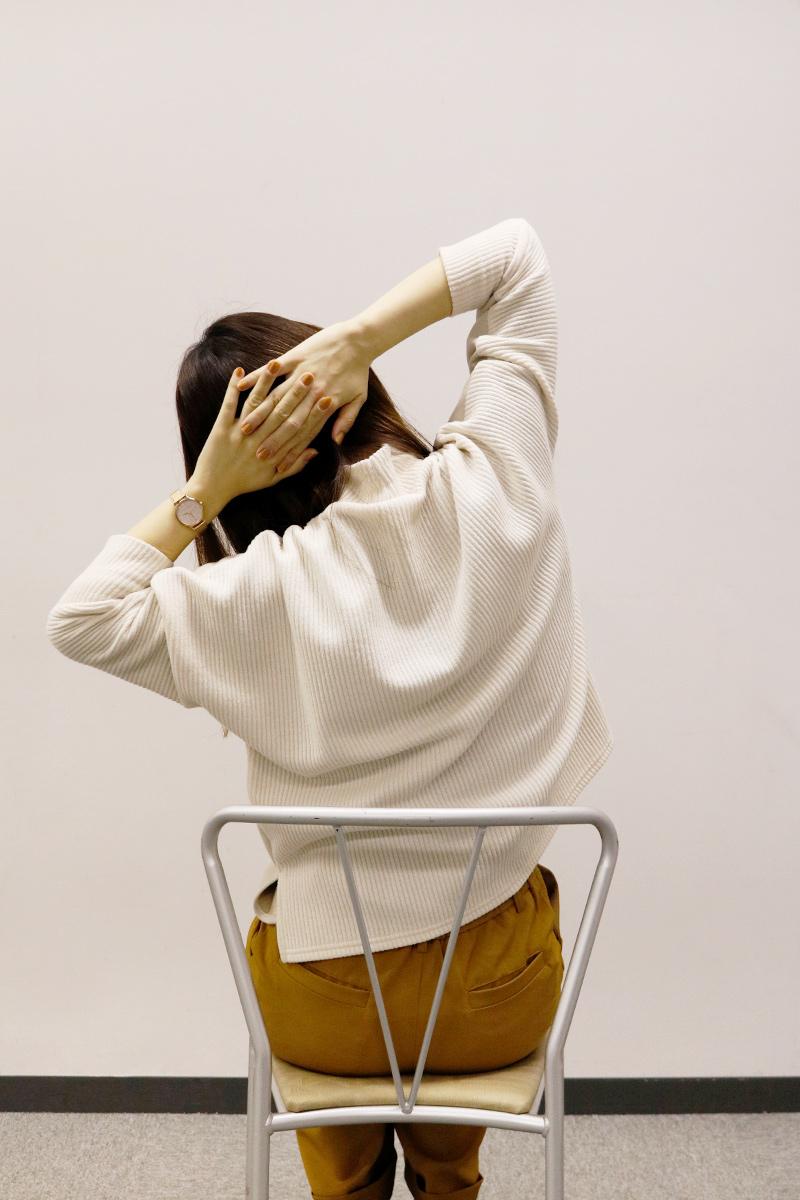 頭の後ろで手を組み体を横に側屈している女性