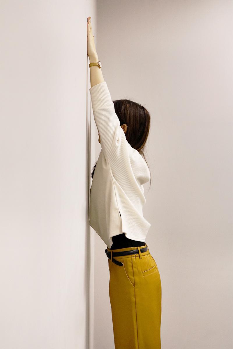 壁に向かって両手を上に広げている女性