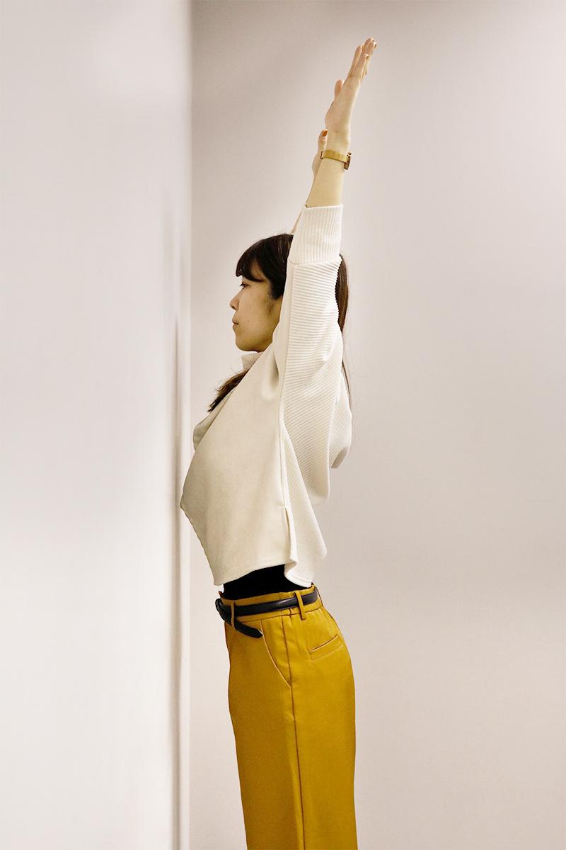 壁に向かって両腕を上げてストレッチしている女性