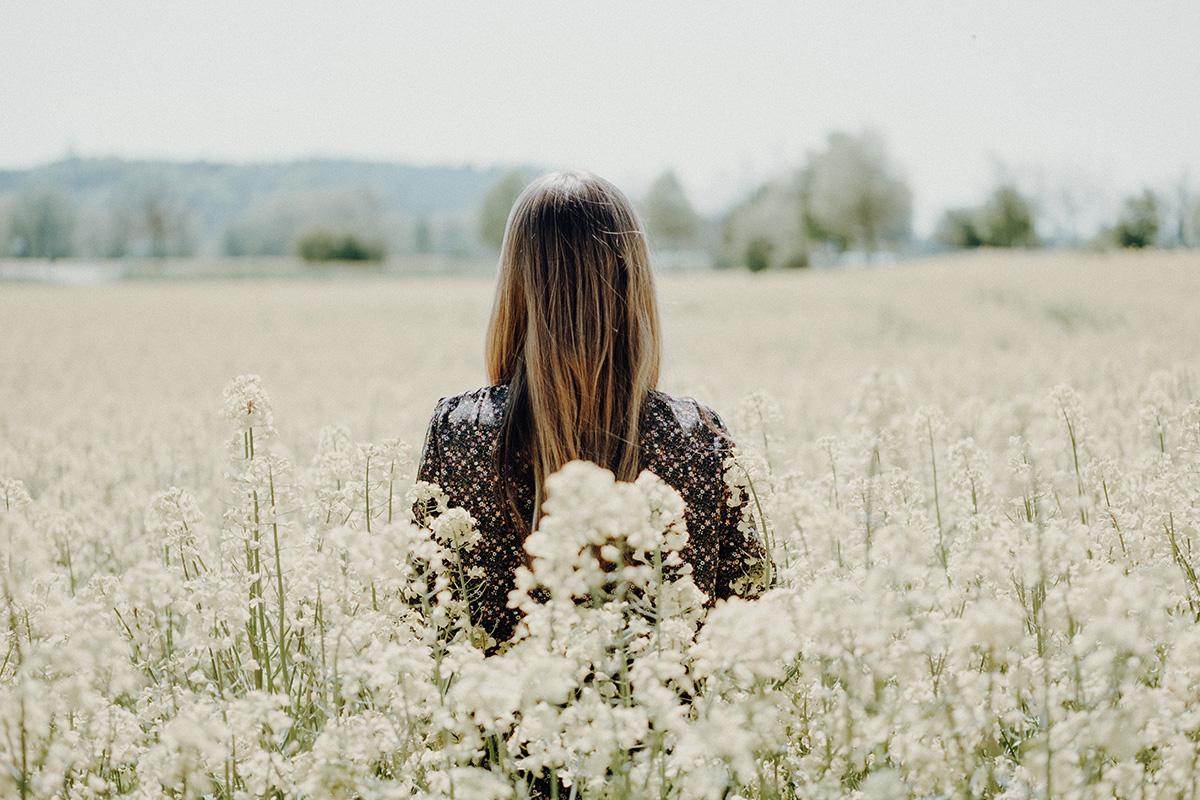 花畑に佇む女性の背中