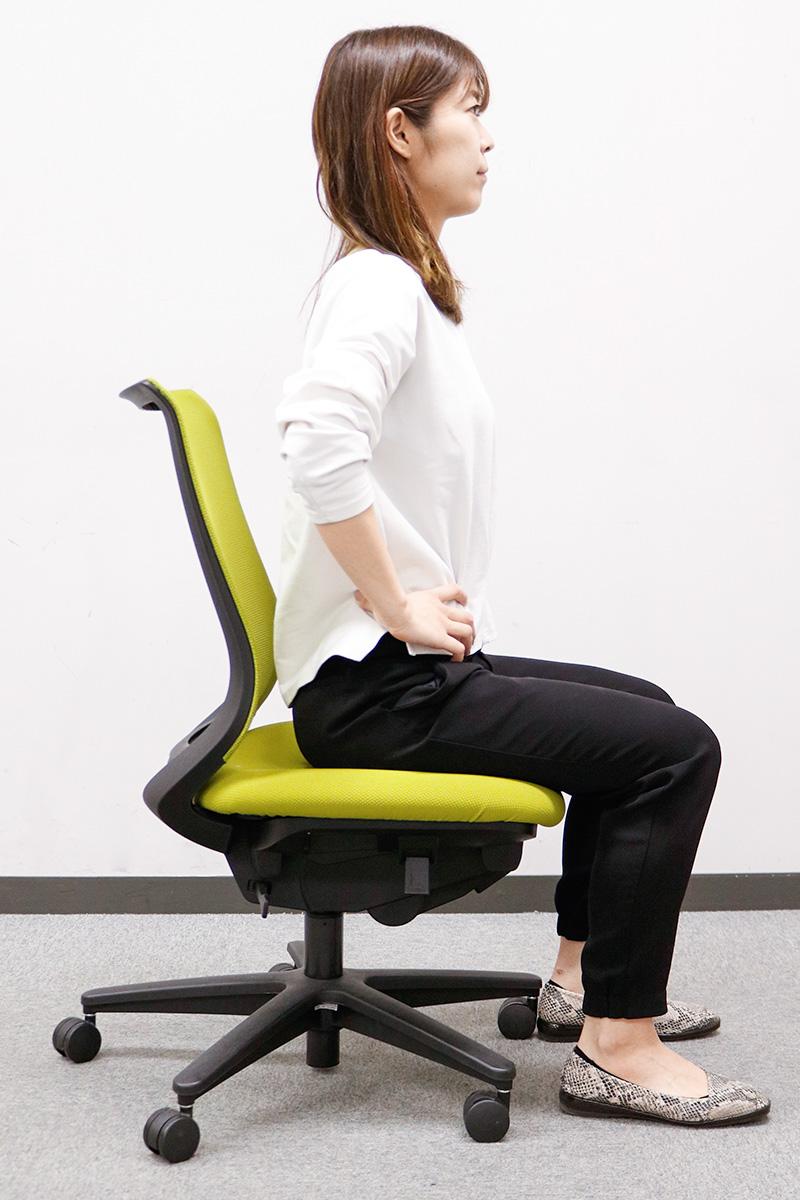 椅子に座って骨盤を触る女性