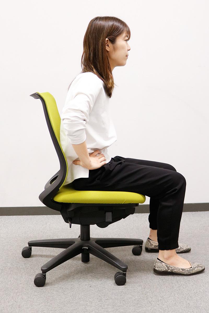 椅子に座って背中を丸める女性