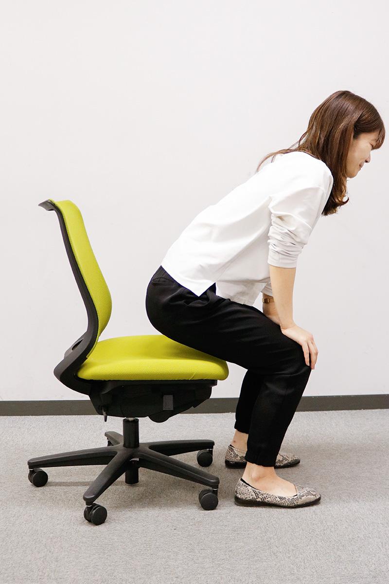 椅子から少しお尻を浮かせている女性