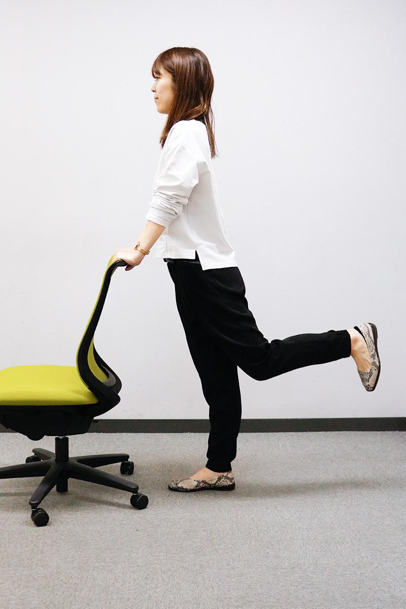 椅子を支えに片足を後ろに伸ばしている女性