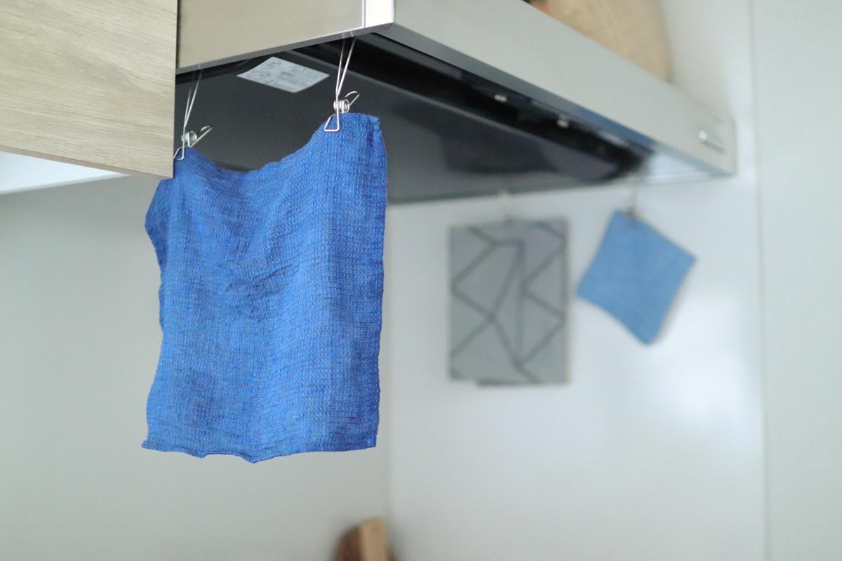 レンジフードの縁にハンギングステンレスピンチで布巾を干す