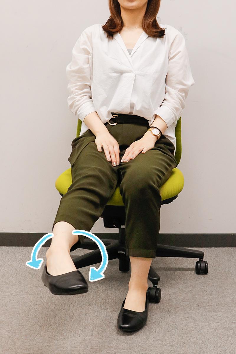 右の足首を回すストレッチをする女性