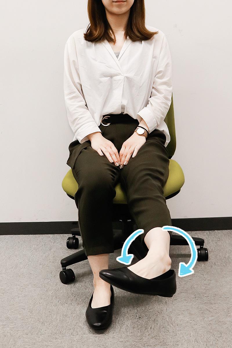 左の足首を回すストレッチをする女性