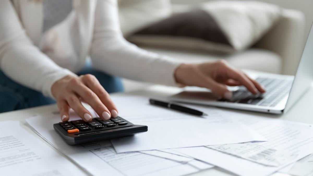 電卓とパソコンでお金管理をする女性