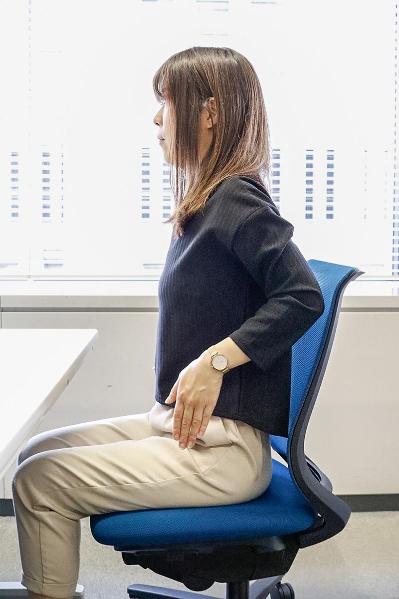 肘を曲げ肋骨あたりに手を添える女性
