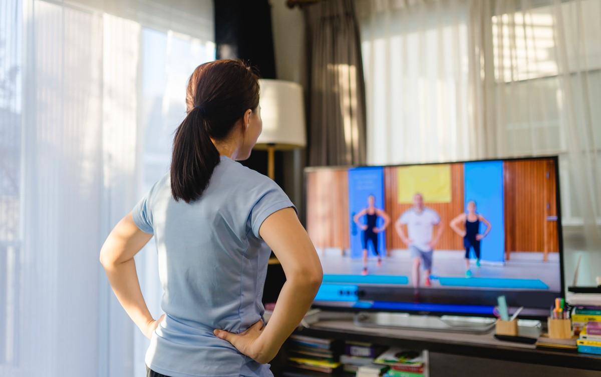 自宅リビングで動画配信型トレーニングを受ける女性