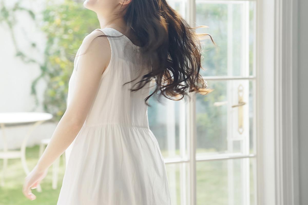 窓辺で髪をなびかせる女性