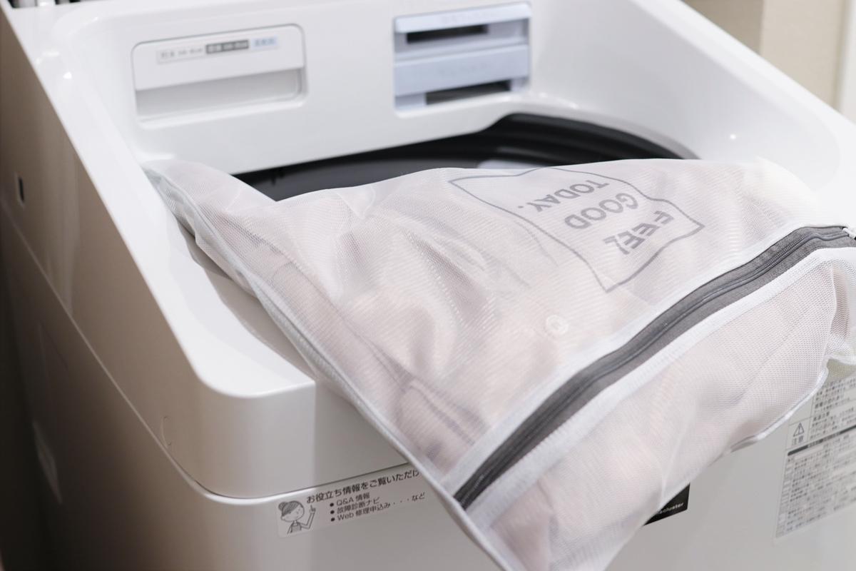 洗濯ネットに入れた服を洗濯機へ入れる