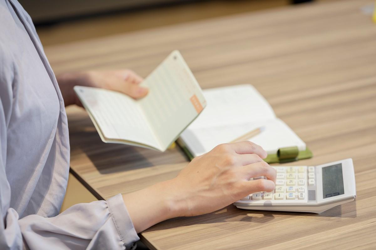 通帳を見ながら家計管理をする女性