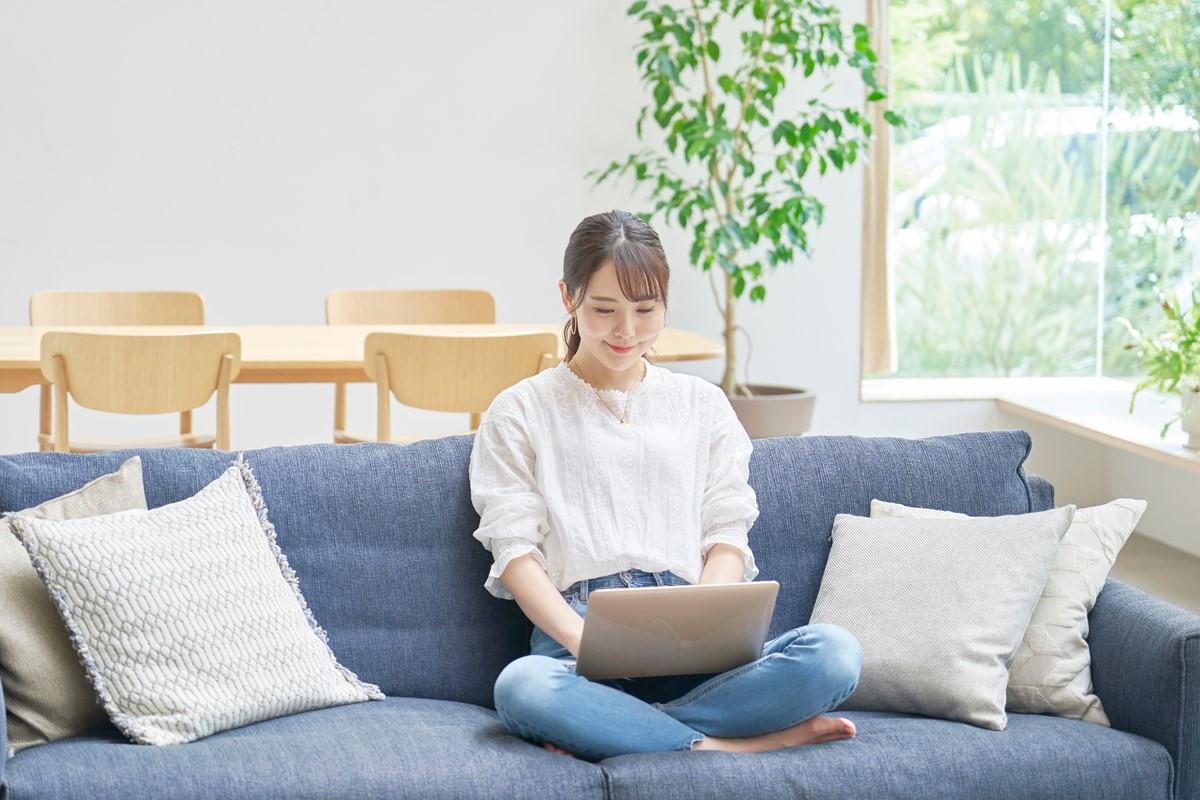 ソファでパソコンを使う女性