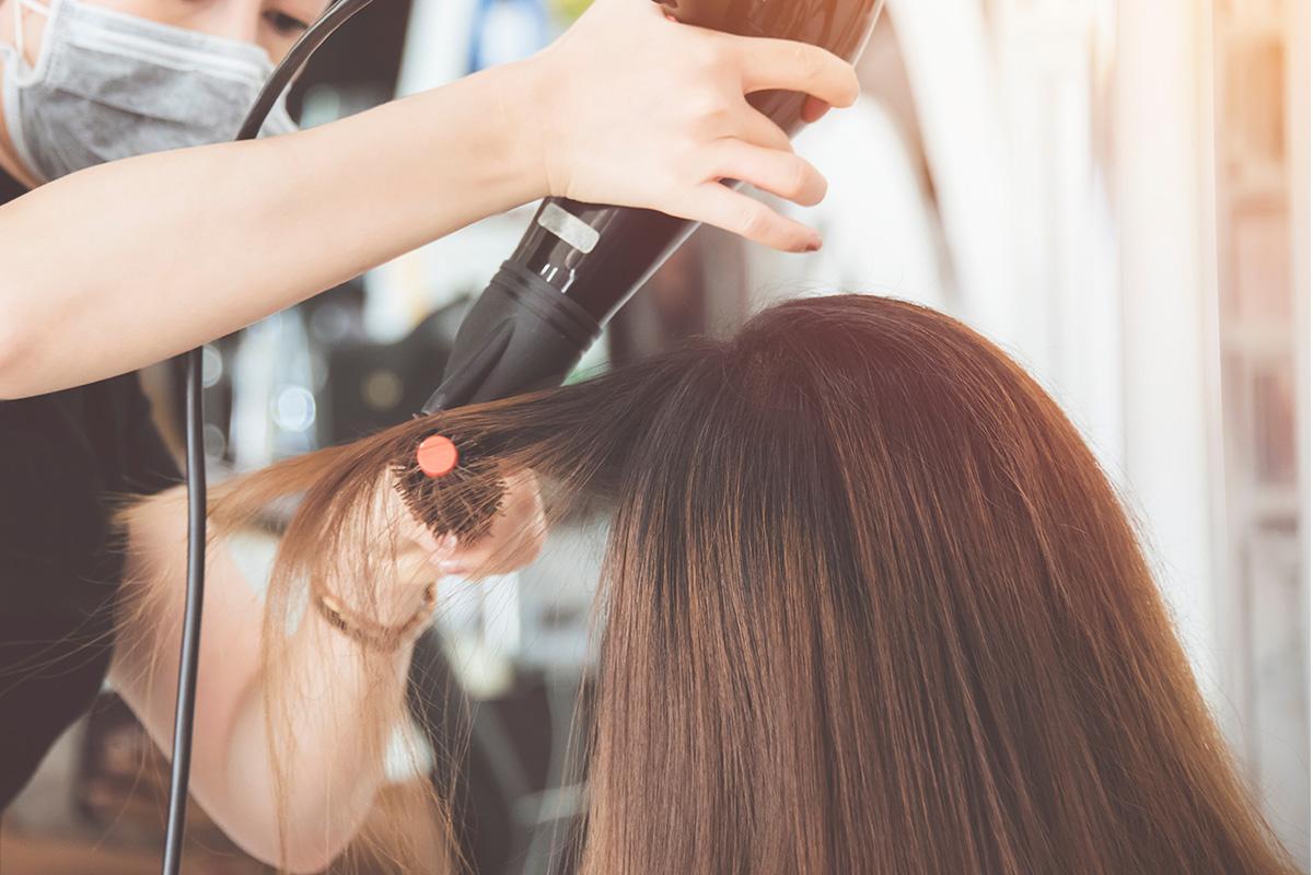 女性の髪の毛をドライヤーで乾かす