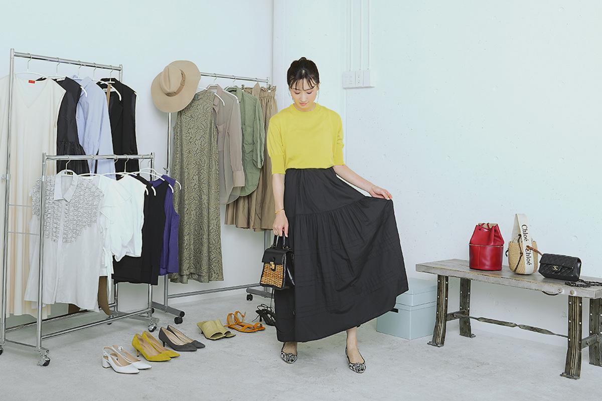 黒のロングスカートのすそを持つモデル