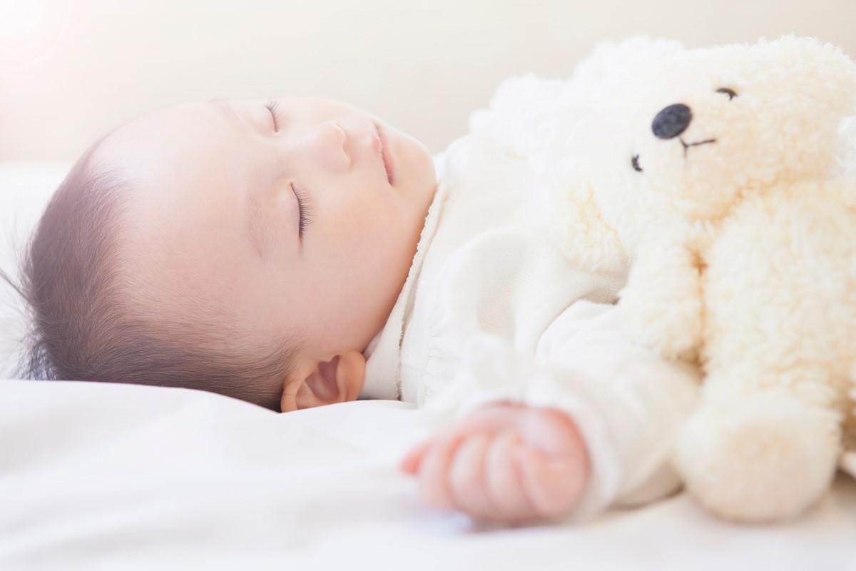 ぬいぐるみと一緒に眠る赤ちゃん